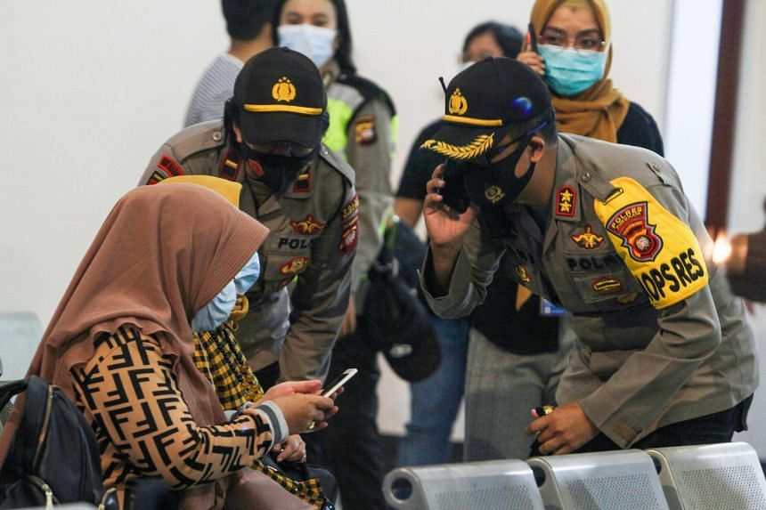 Relatives of passengers on board the missing plane wait for news at the Supadio airport in Pontianak on Jan 9, 2021.