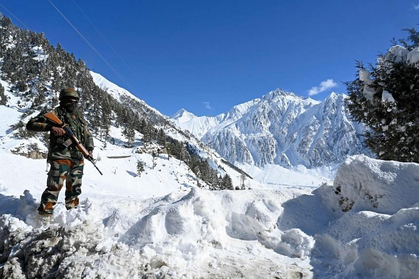 An Indian army soldier stands on a snow covered road after snowfall near Zojila mountain pass that connects Srinagar to the union territory of Ladakh, bordering China on Nov 26, 2020.