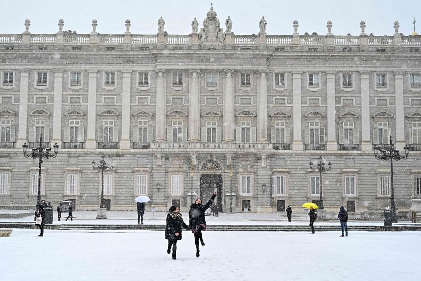 Two girls run in the snow outside the Royal Palace in Madrid, on Jan 8, 2021.