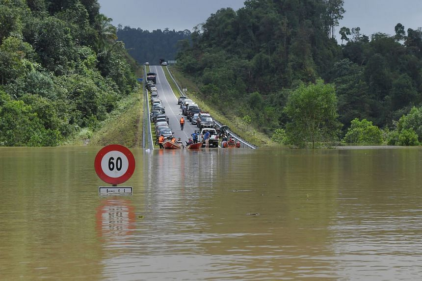 A road connecting Bandar Al-Muktafi Billah Shah in Malaysia's Terenggnau state to three villages inundated with flood water yesterday. The number of flood victims in the east coast state totalled 12,899 yesterday morning. PHOTOS: BERNAMA