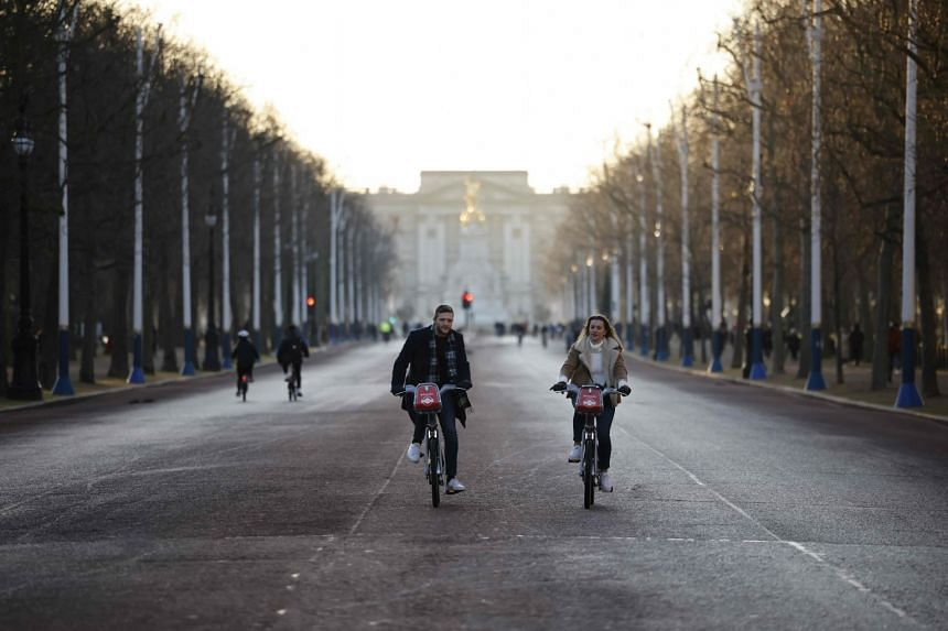 People cycle on the Mall with Buckingham Palace in the background in London, on Jan 9, 2021.