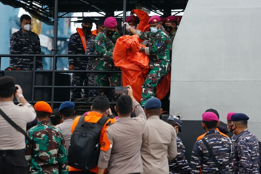Indonesian rescue members carry what is believed to be the remains of Sriwijaya Air Flight SJ182 at Jakarta International Container Terminal port on Jan 10, 2021.