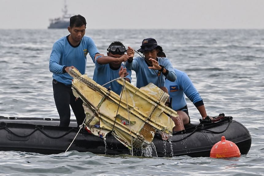 Indonesian Navy divers hold wreckage from Sriwijaya Air Flight SJ182 during a search and rescue operation at sea near Lancang island on Jan 10, 2021.