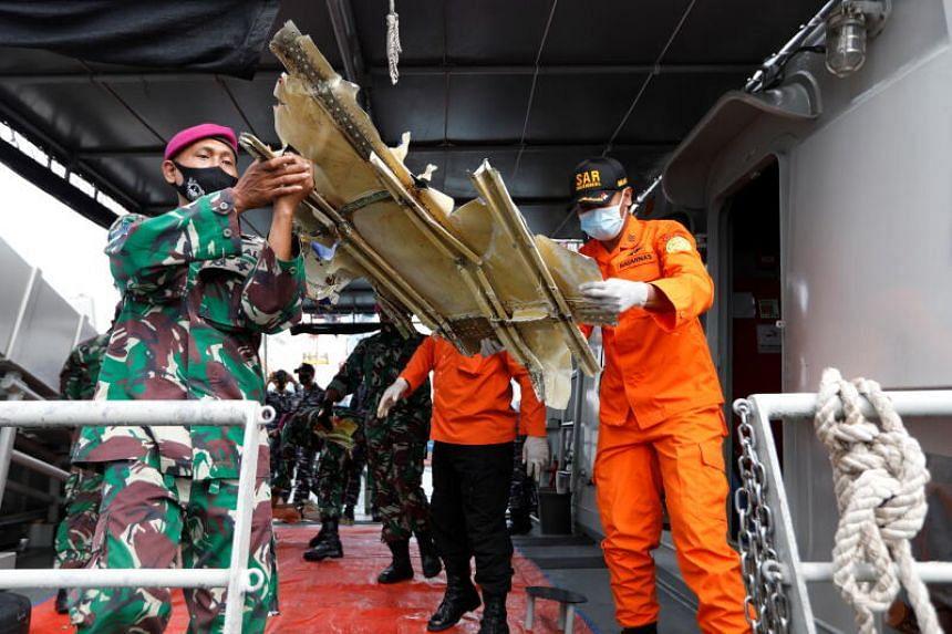Navy personnel and rescue members carry debris of Sriwijaya Air Flight SJ182 as they arrive at Tanjung Priok port in Jakarta, on Jan 10, 2021.