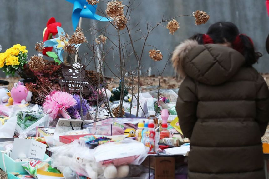 A child pays tribute to little Jung-in in a cemetery in Yangpyeong, South Korea, on Jan 4, 2021.
