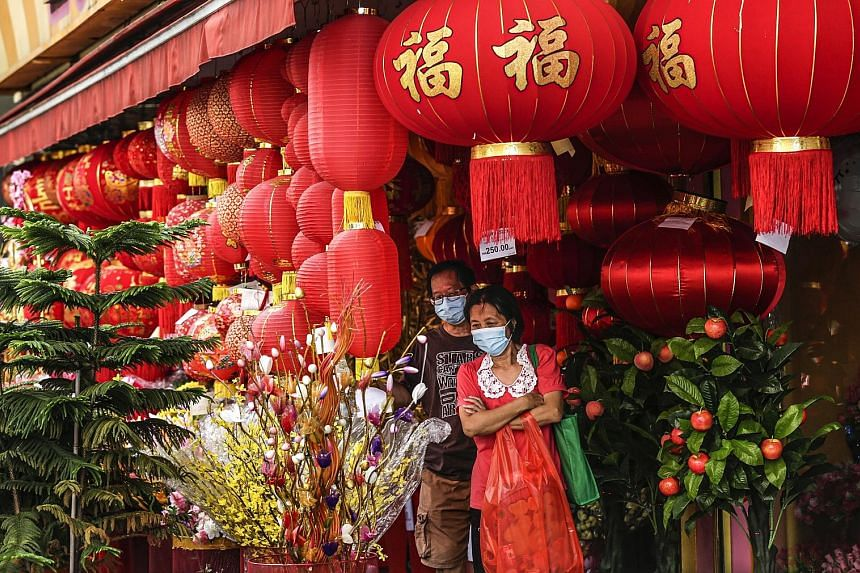 People shopping for festive decorations in Kuala Lumpur last Friday. Major Chinese groups in Malaysia have implored those celebrating Chinese New Year to restrict visits and gatherings, amid the high number of daily Covid-19 cases.