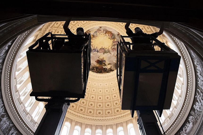 Workers preparing for President-elect Joe Biden's Jan 20 inauguration in the Capitol Rotunda on Capitol Hill in Washington on Friday. Mr Biden has urged his supporters not to travel for the inauguration, because outside of the swearing-in ceremony, t