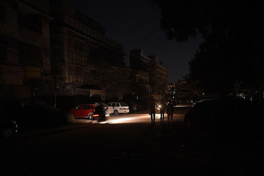 People walking through a residential area during a power blackout in Karachi early yesterday. This was Pakistan's second major power breakdown in less than three years. PHOTO: AGENCE FRANCE PRESSE
