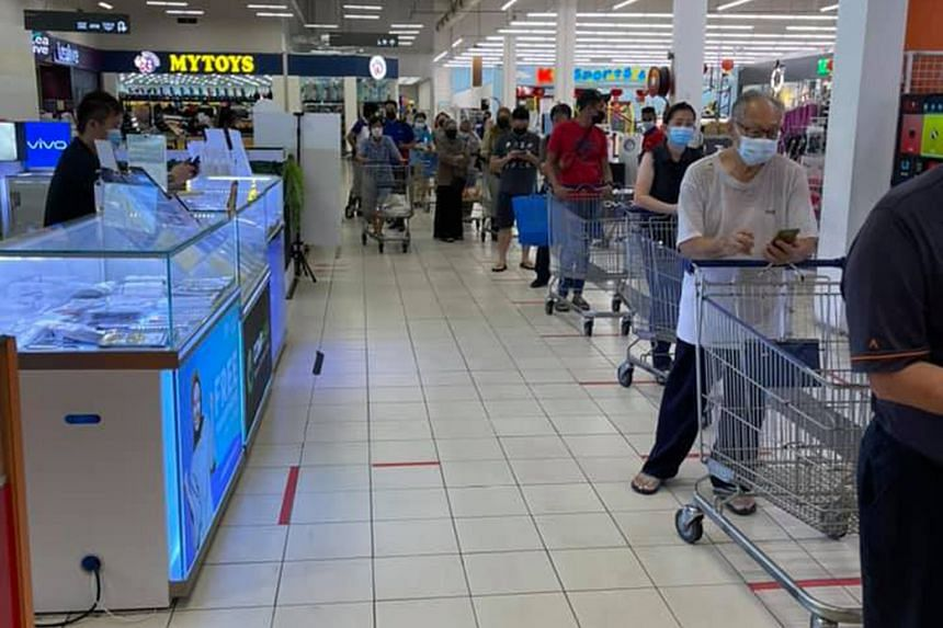 Shoppers queueing to enter a Tesco supermarket in the Kuala Lumpur suburb of Cheras last Friday. Two Cabinet ministers issued statements yesterday urging shoppers not to panic buy.