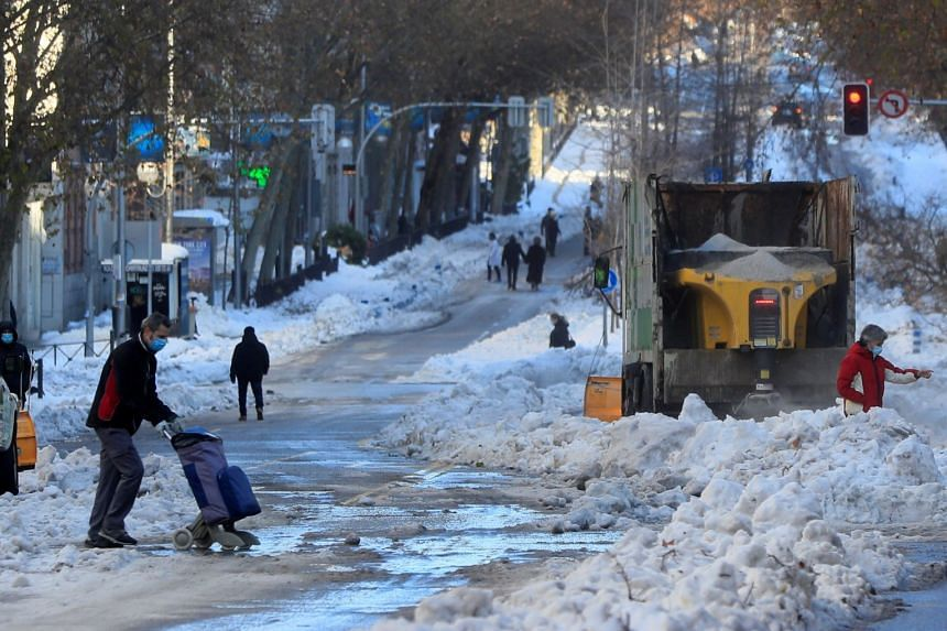 A man crosses a street as a snowplough clears the snow in Madrid, on Jan 11, 2021.