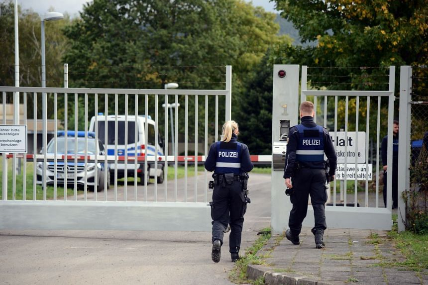 Policemen walk in front of the entrance gate to the former Nato bunker (not visible), where an illegal computer centre was discovered.