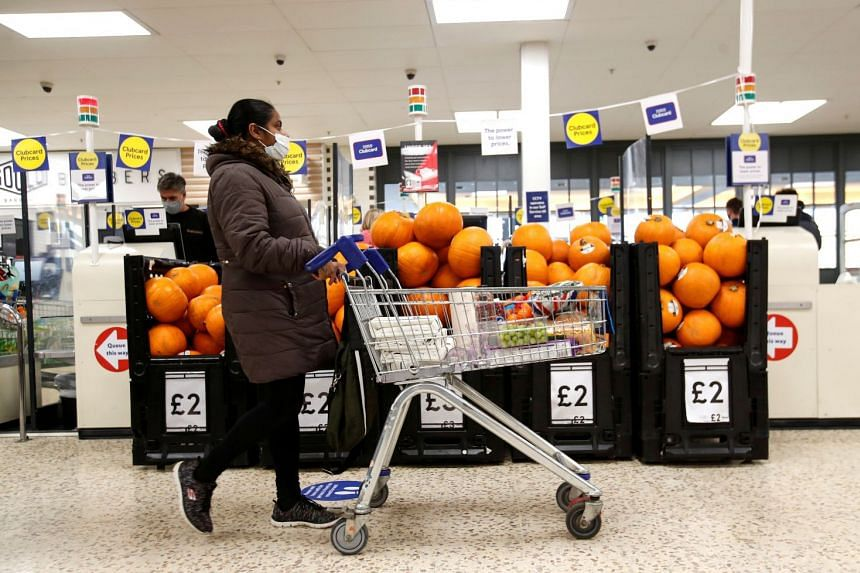 A woman pushes a shopping cart at a Tesco supermarket in Hatfield, Britain.