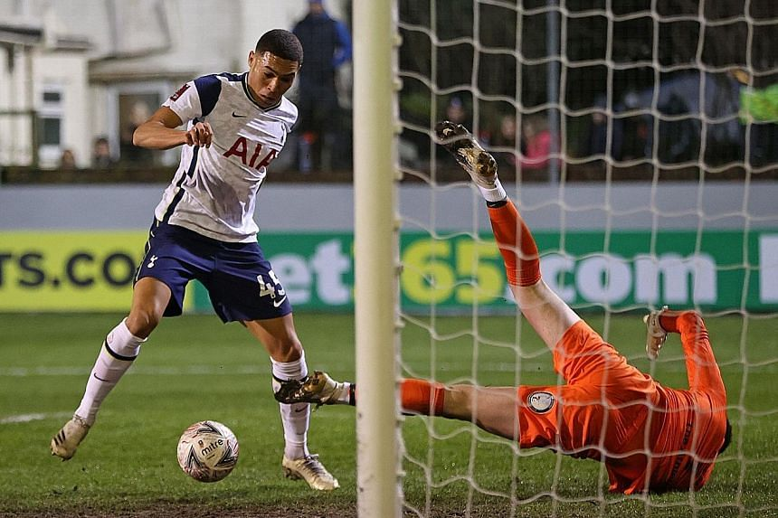 Tottenham Hotspur striker Carlos Vinicius beating Marine goalkeeper Bayleigh Passant to score the opening goal of their English FA Cup third round match at Rossett Park. The Brazilian player added two more for a first-half hat-trick as Spurs clinched