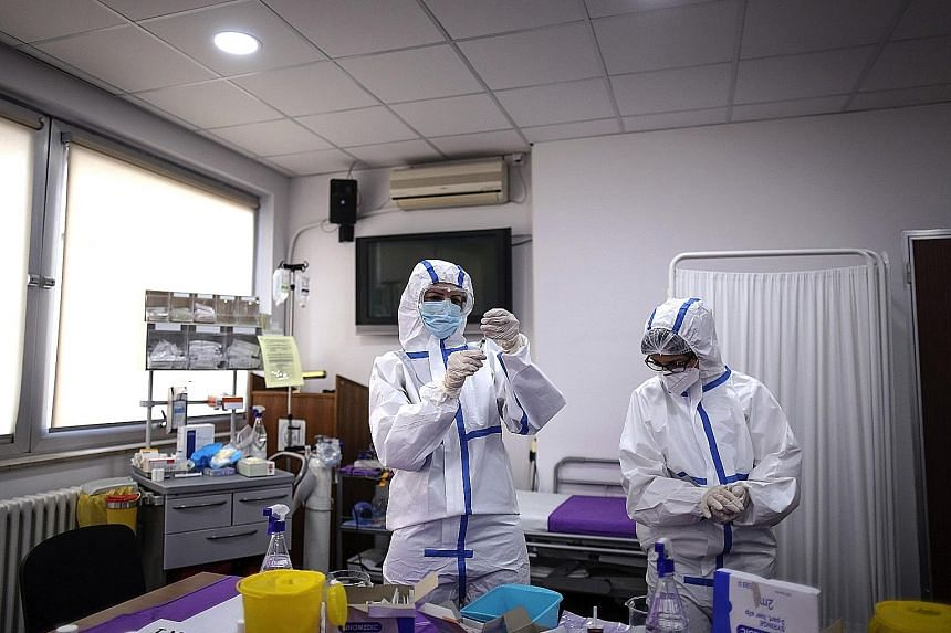 Workers preparing doses of the Pfizer-BioNTech vaccine in Serbia. The pandemic has given the world common cause to work together, says DPM Heng, with institutions cooperating across borders on treatments and vaccines.