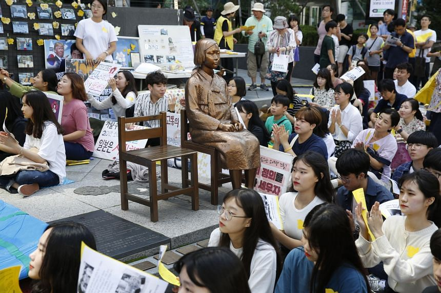South Korean supporters of former 'comfort women' gather around a statue symbolizing a wartime sex slaves near the Japanese Embassy in Seoul on Sept 11, 2019.