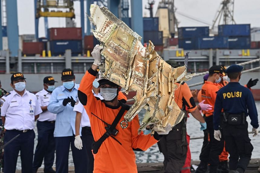 A search and rescue team member with a part of the plane's wreckage recovered from the sea yesterday. The joint operation team has managed to narrow the search area thought to be the location of the black box.