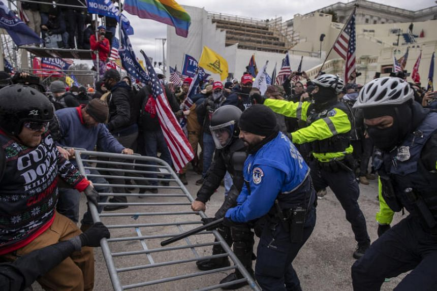 Demonstrators and US Capitol police battle fight over a barricade in Washington on Jan 6, 2021.