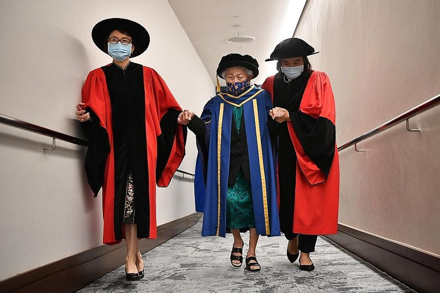 Dr Oon Chiew Seng being accompanied by Adjunct Associate Professor Helen Chen (left) and her caregiver as she was leaving the University Cultural Centre, where she received the Honorary Degree of Doctor of Letters yesterday. ST PHOTO: CHONG JUN LIANG