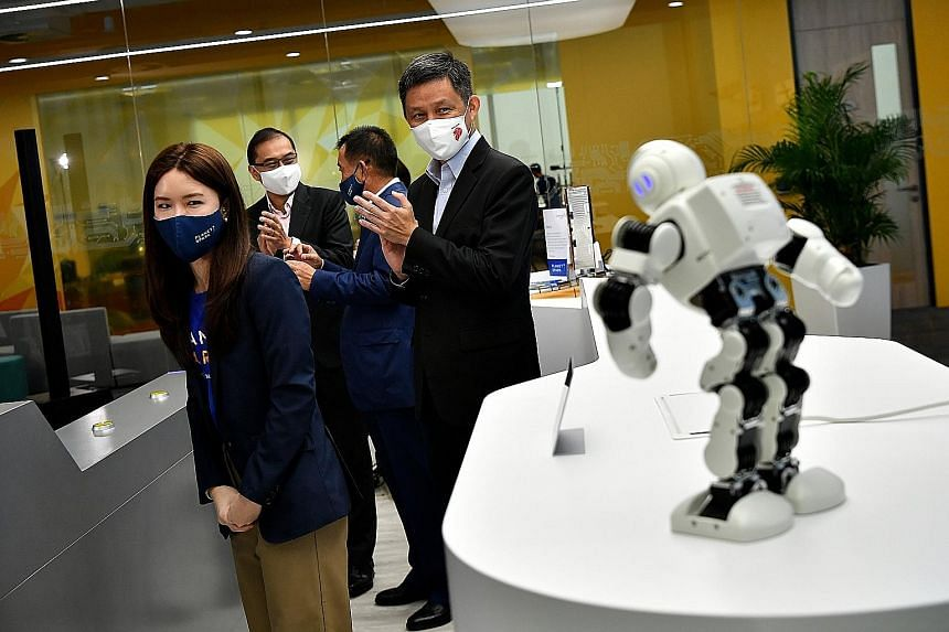 Trade and Industry Minister Chan Chun Sing and investment company PlanetSpark managing director Phuay Li Ying watching the company mascot's performance at the launch of the PlanetSpark Innovation Centre yesterday. Behind them are JTC Corporation chie