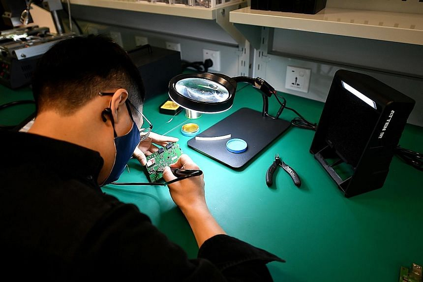 PlanetSpark senior engineer Zhou Xiang, 32, debugging hardware in a test lab at PlanetSpark Innovation Centre's launch yesterday.