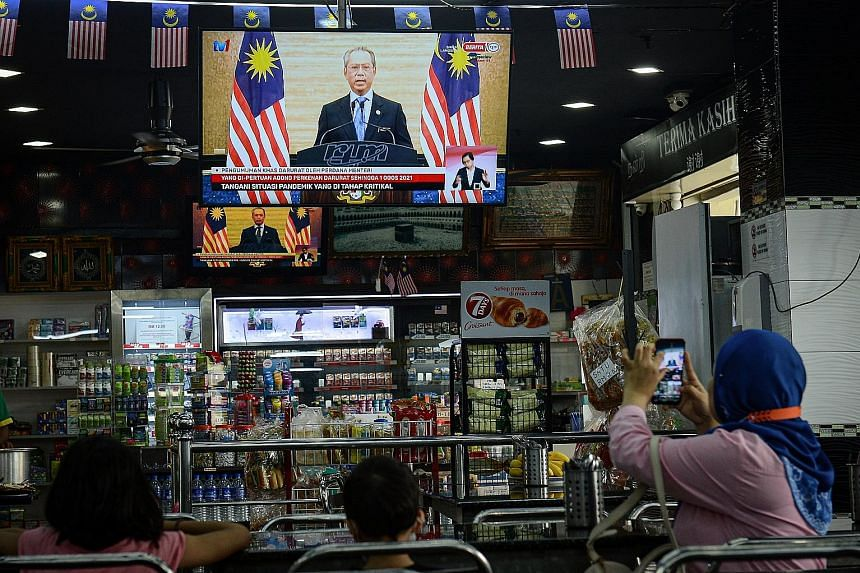 Kuala Lumpur residents watching yesterday's live national address by Prime Minister Muhyiddin Yassin where he announced the state of emergency and sought to instil calm, saying that the government and public services would continue to function normal