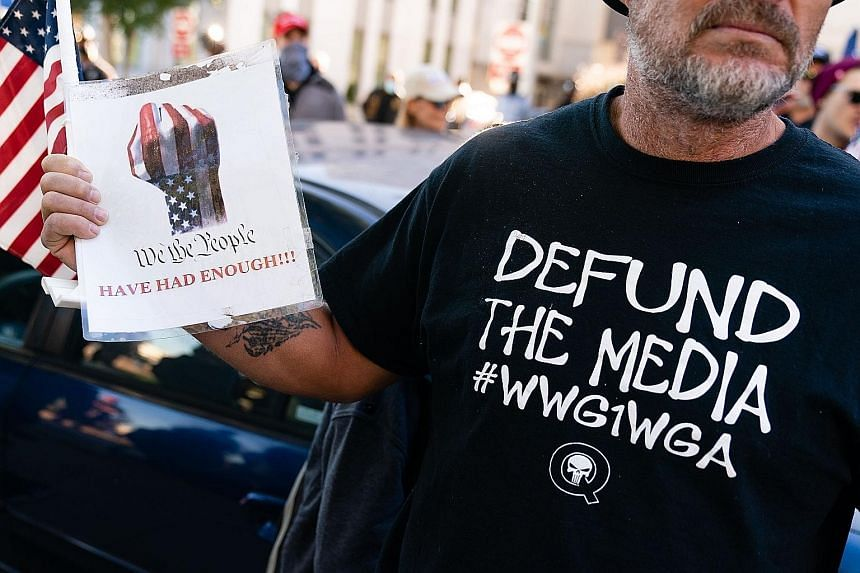 "A QAnon conspiracy theory supporter wearing a ""Defund the media"" QAnon shirt at a ""Stop the steal"" rally against the results of the US presidential election outside Georgia's state capitol in Atlanta on Nov 18 last year."