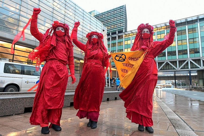 Environmental activists protesting in The Hague, Netherlands, during the hearing of a case that environmentalist and human rights groups brought against Royal Dutch Shell, to force the energy firm to cut its reliance on fossil fuels, on Dec 1. The ba