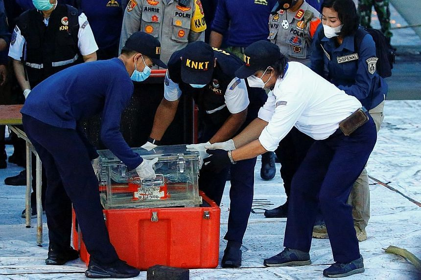 Indonesian National Transportation Safety Committee officials handling part of the recovered flight data recorder, which contains key data like airspeed and altitude, in Jakarta yesterday. PHOTO: REUTERS