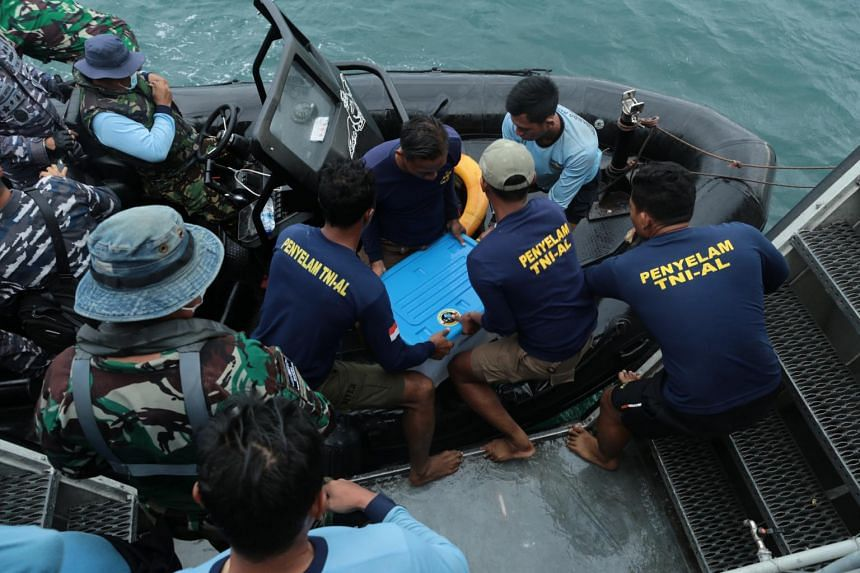 Indonesian Navy personnel move a plastic container carrying a black box of the crashed Sriwijaya Air plane on Jan 12, 2021.