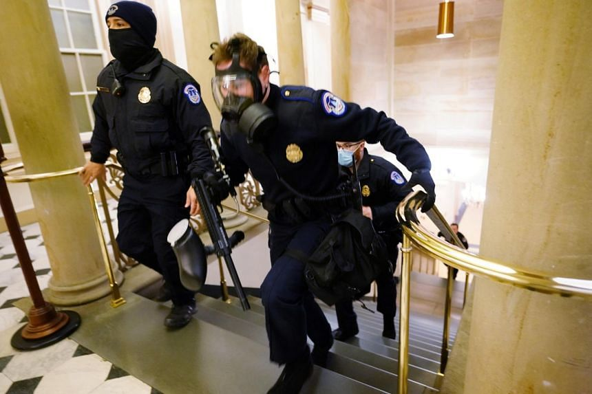 US Capitol police officers are seen taking position as protesters storm the building in Washington on Jan 6, 2021.