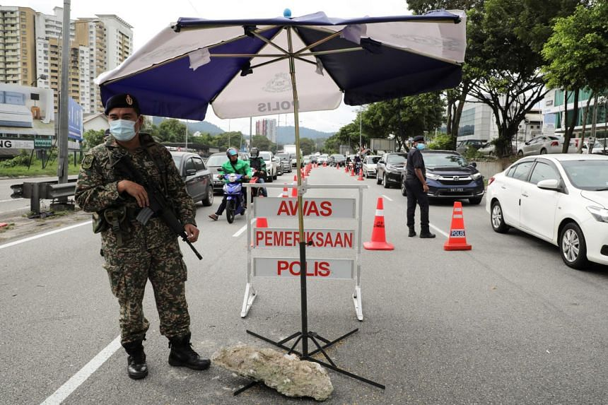 A soldier stands guard at a roadblock to enforce lockdown measures in Kuala Lumpur, on Jan 13, 2021.
