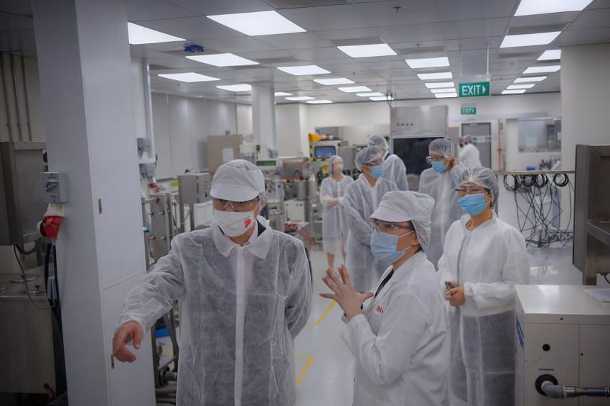 Ms Xue Si-Ying (right) showing Trade and Industry Minister Chan Chun Sing around, during a tour of the Dairy and Beverage Lab at DuPont Singapore on Jan 13, 2021.
