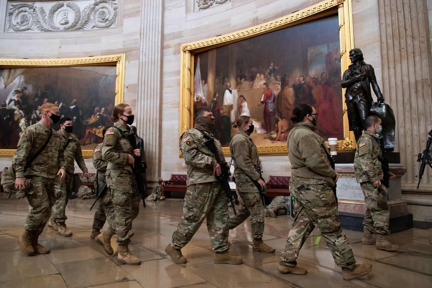 Members of the National Guard walk through the Rotunda of the US Capitol in Washington on Jan 13, 2021.