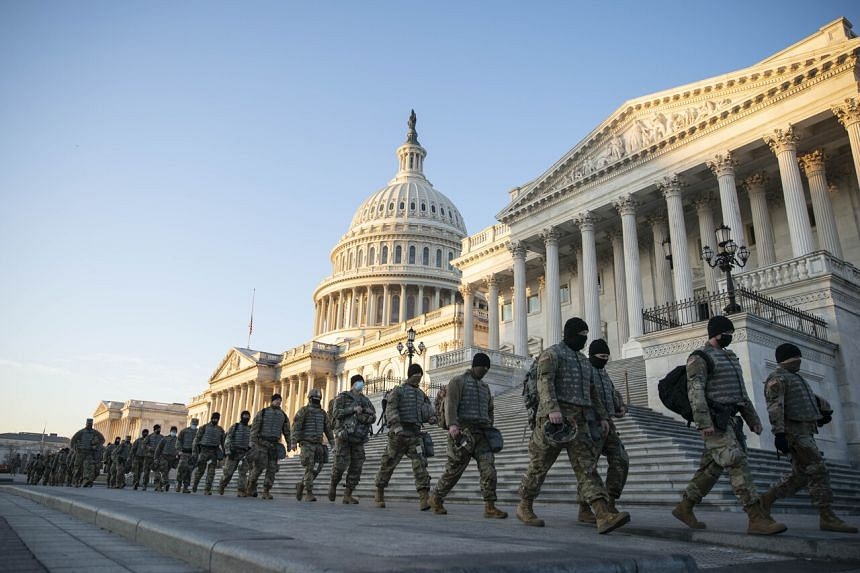 Members of the National Guard walk outside of the US Capitol in Washington on Jan 13, 2021.