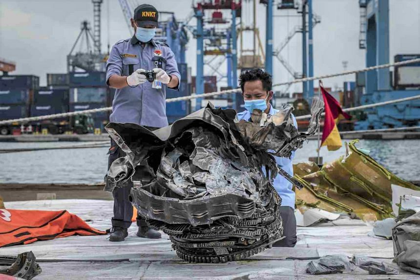 Safety officials examine wreckage from the Sriwijaya Air plane that crashed in the Java Sea, in Jakarta on Jan 12, 2021.