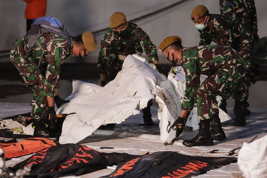Indonesian military personnel carry the debris of the Sriwijaya Air flight SJ 182 at Tanjung Priok port in Jakarta, Jan 13, 2021.