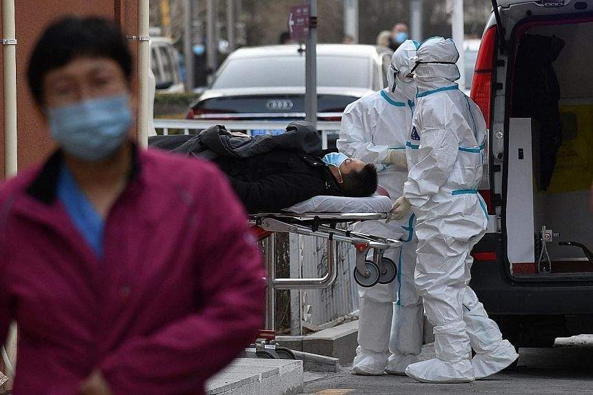 Medical workers wearing protective suits moving a patient to the fever clinic at a hospital in Beijing yesterday. Most of the new patients were reported near the capital city, but a province in north-east China also saw a rise in new cases. There wer
