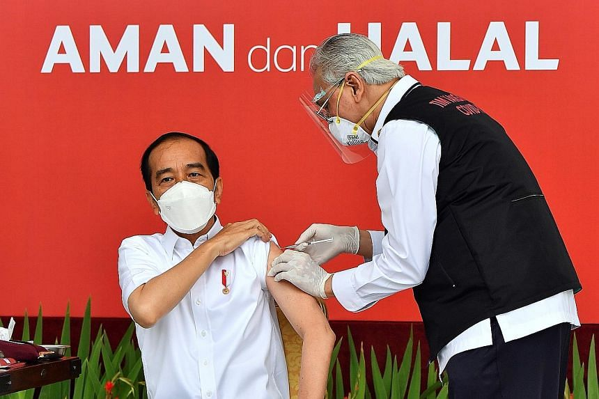 Indonesian President Joko Widodo receiving his first dose of the vaccine developed by China's Sinovac Biotech at the presidential palace in Jakarta yesterday. Mr Joko was the first person in the country to have a Covid-19 shot, to give Indonesians th