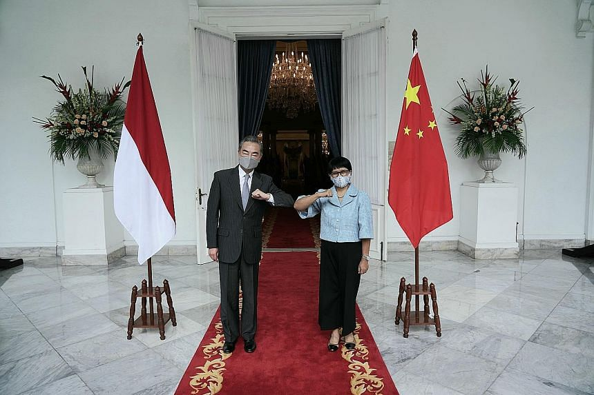 """Chinese Foreign Minister Wang Yi with Indonesian Foreign Minister Retno Marsudi in Jakarta yesterday. Mr Wang said China """"is prepared to continue (vaccine) production cooperation with Indonesia... and will support Indonesia to become a regional produ"""