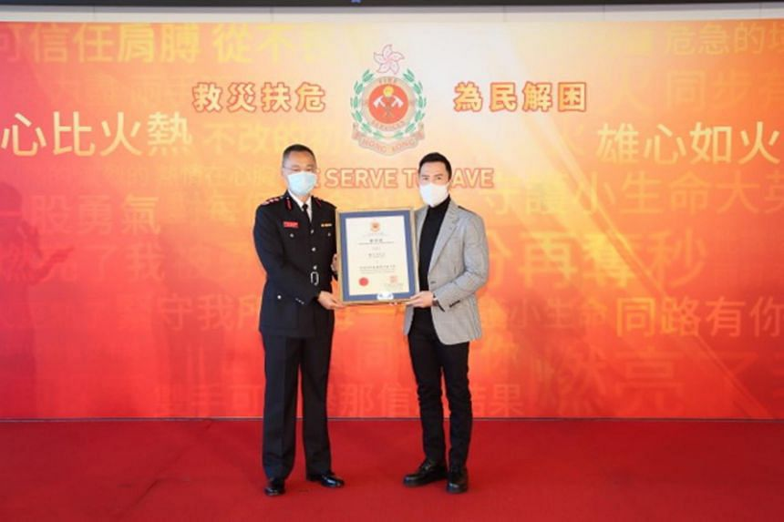 Hong Kong Fire Services director Joseph Leung (left) presenting the appointment certificate to Donnie Yen.