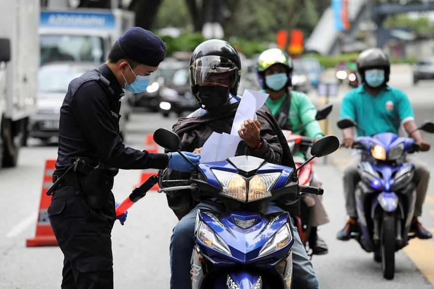 A police officer checks the documents of a rider at a roadblock in Kuala Lumpur, on Jan 13, 2021.
