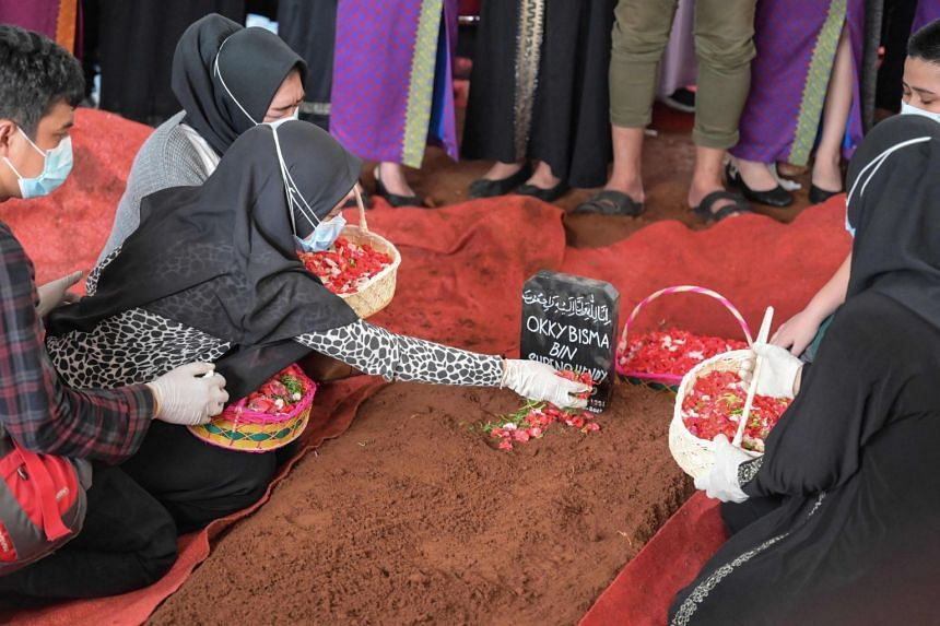 Aldha Refa (second from left), the wife of Okky Bisma, places petals over his grave during his funeral in Jakarta on Jan 14, 2021.