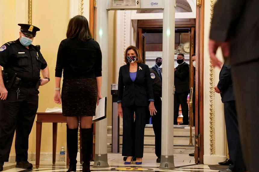 US House Speaker Nancy Pelosi walks through a new metal detector outside the House chamber in the Capitol in Washington on Jan 12, 2021.