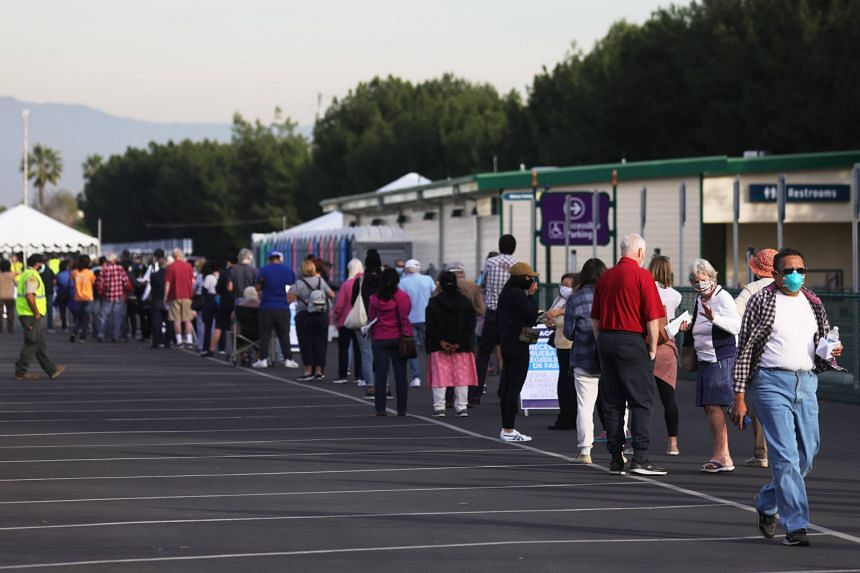 People wait in line at a parking lot at Disneyland Resort to receive the Covid-19 vaccine, on Jan 13, 2021.