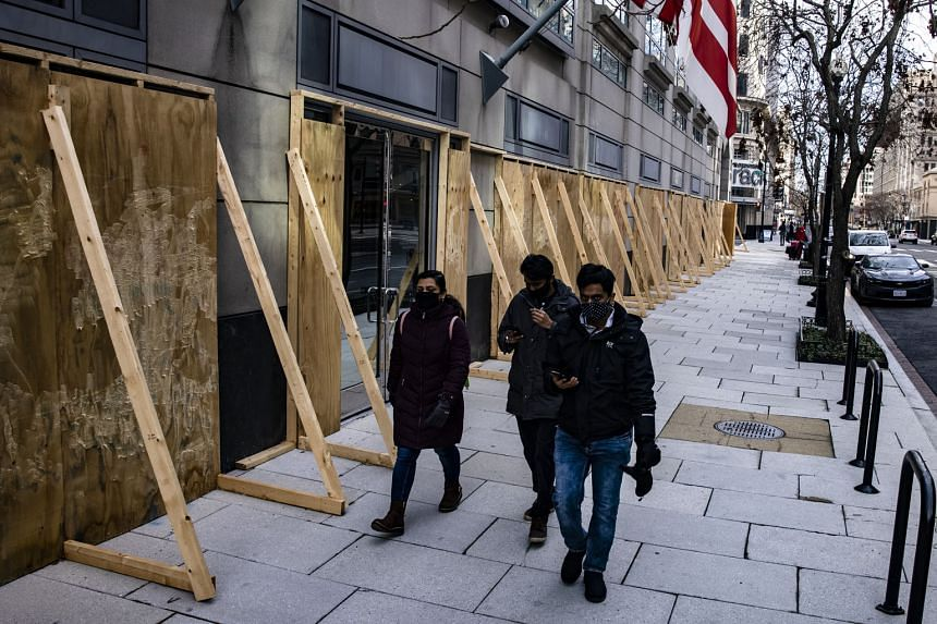 Pedestrians walking past a boarded-up office building in Washington on Jan 2. Many buildings in the city of more than 700,000 have been boarded up due to pandemic closures or riots. Troop deployment has also been increased in the lead-up to Mr Joe Bi