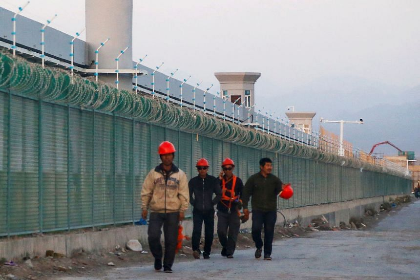 A 2018 photo of workers walking past what is officially known as a vocational skills education centre in Xinjiang. Beijing says such centres operate to counter Islamist radicalism following a series of attacks it attributed to the Uighurs. PHOTO: REU