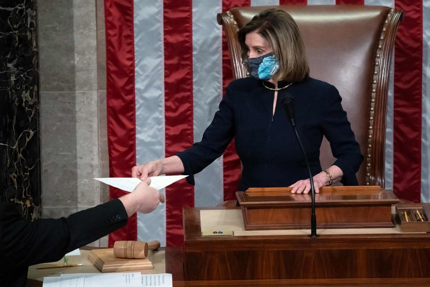 Speaker Nancy Pelosi presides over the House of Representatives as they conclude the vote to impeach US President Donald Trump.