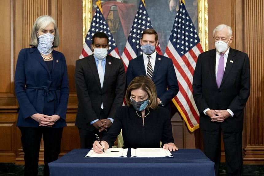 US Speaker of the House Nancy Pelosi signs an article of impeachment against President Donald Trump, while impeachment managers look on, at the Capitol in Washington on Jan 13, 2021.