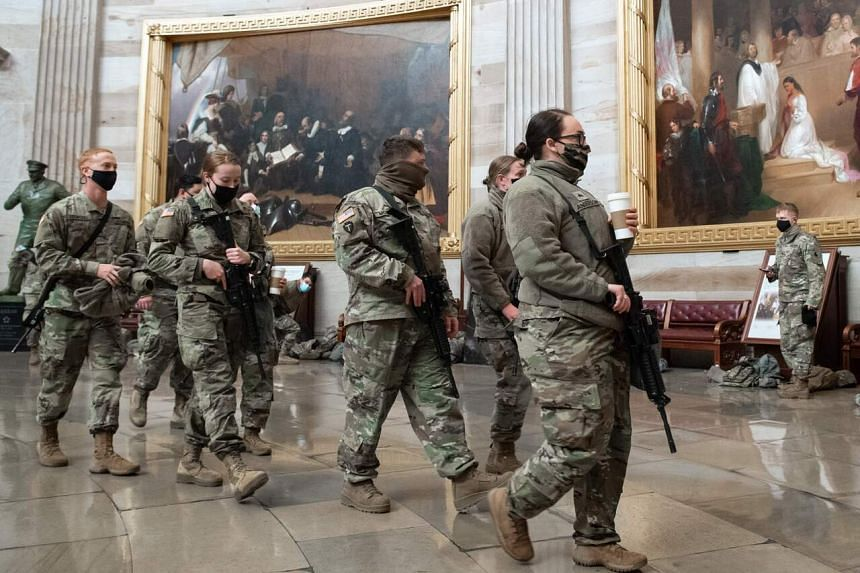 Members of the US National Guard walk through the Rotunda of the Capitol in Washington on Jan 13, 2021.