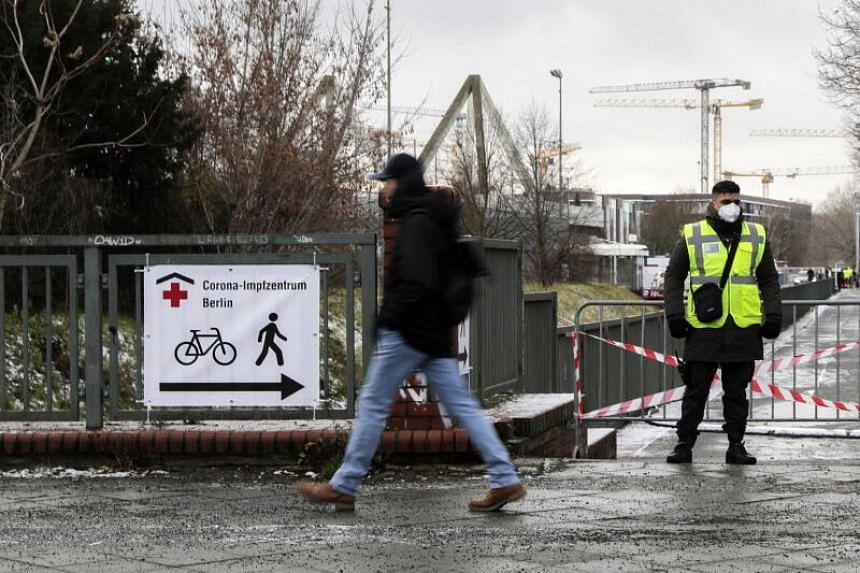 A man walks past a sign reading 'Corona Vaccine Centre Berlin' at the Erika Hess Ice Stadium, on Jan 14, 2021.